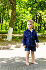 Handsome barefoot little boy standing waiting