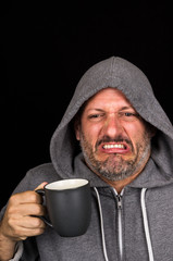 Portrait of disgusted man drinking a cup of coffee