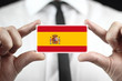 Businessman holding a business card with Spain Flag