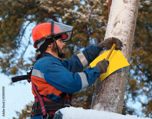 Electrician attaches to an electricity pylon yellow sign