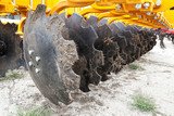 Closeup of cultivator knives of plowing tractor with dirt