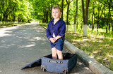 Cute young boy standing in an open suitcase