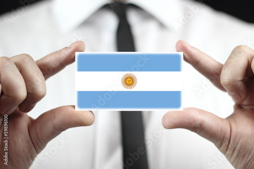 Businessman holding a business card with Argentina Flag