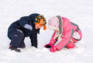 Young brother and sister playing in the snow