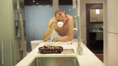 Man in towel after shower reading magazine by table in kitchen
