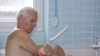 Senior man washing his body with soap sponge in bath.