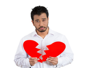 Sad, lonely man holding a broken heart