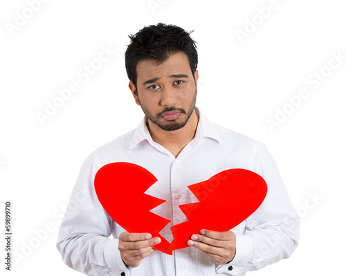 Sad, lonely man holding a broken heart