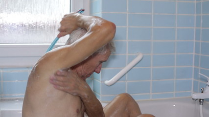 Senior man washing his body with bath brush.