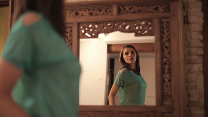 Young woman checking her look in front of the mirror