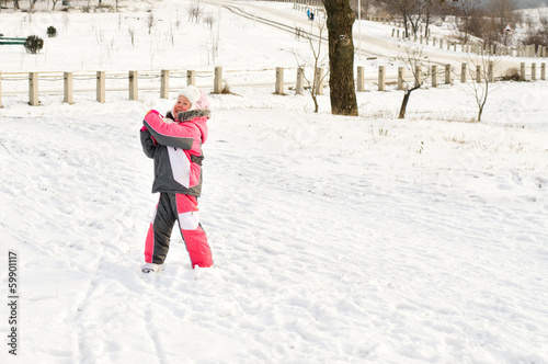 Cute little brother and sister hugging in the snow