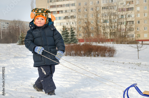 Cute little boy pulling his sled