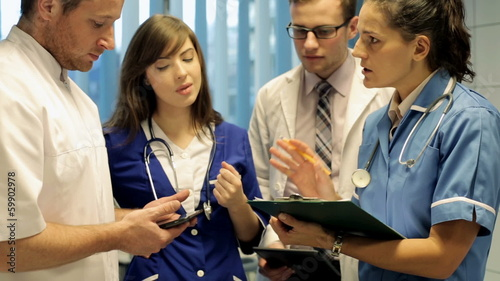 Young group of doctors discussing over documents