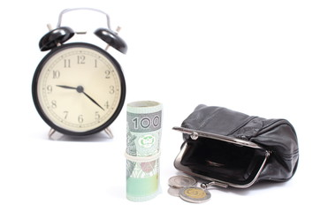 Roll of tied banknotes and coins with retro styled alarm clock