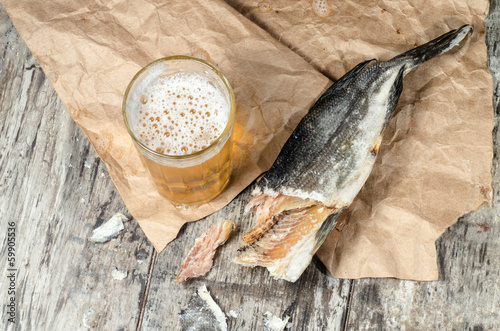 Dry fish with beer on wrapping paper