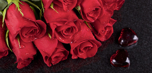 Red roses and two red glass hearts on black ceramic background