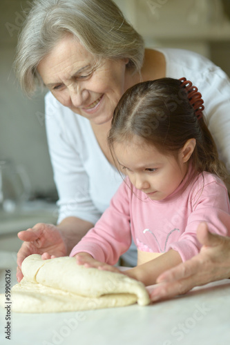 Little girl kneading dough with grandmother
