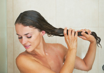 Young woman washing hair in shower