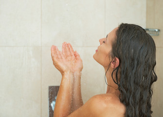 Young woman washing in shower. rear view