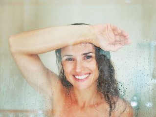Happy young woman behind shower door