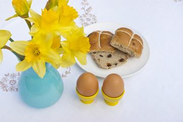 Easter breakfast, eggs, hot cross buns, daffodils.