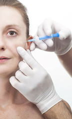Woman getting botox injection to remove eye wrinkles