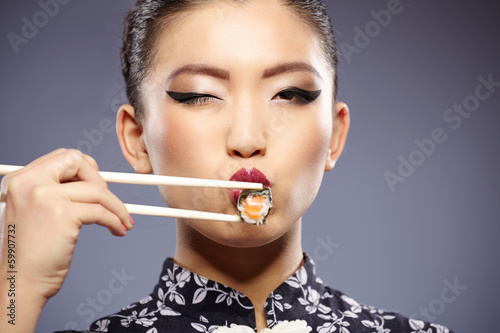 Sushi woman holding sushi with chopsticks looking at the camera - 59907732