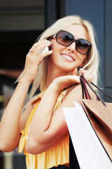 Happy blond woman with shopping bags calling on the phone
