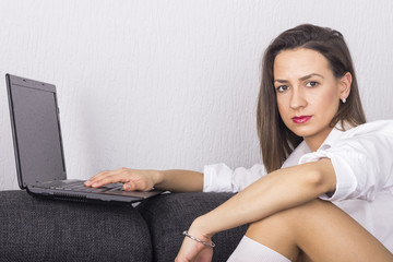 Young beautiful woman lying on a bed and using laptop