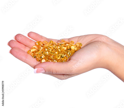Vitamin A Capsules in Female Hand isolated on white background.