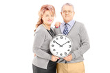 Portrait of middle aged couple holding wall clock