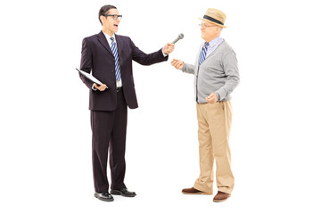 Young man conducting survey on middle aged man with microphone