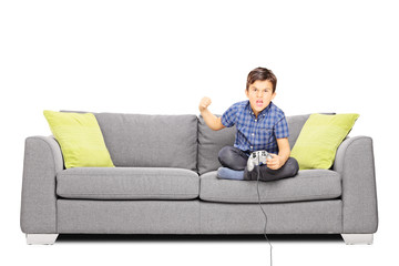 Nervous kid sitting on sofa and playing video games