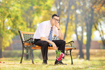 Sad guy holding a bouquet of flowers on a bench in a park