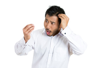 Shocked man feeling head, surprised he is losing hair