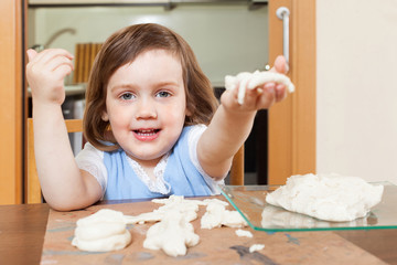 Little girl sculpts dough figurines
