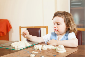 Little girl makes dough figurines