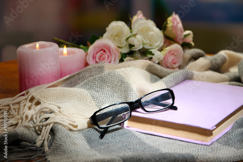 Composition with old book, eye glasses, candles and plaid