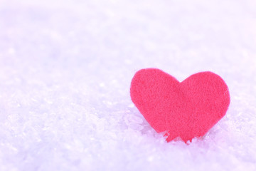 Little felt heart on snowy background