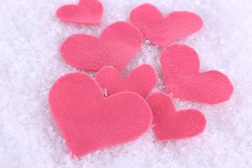 Little felt hearts on snowy background