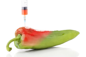 Paprika in two colors with a syringe. Concept for GMO.