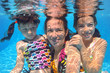 Happy family swim underwater in pool and having fun