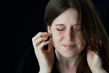 young woman holding earlobes with frown