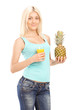 Smiling young female holding pineapple and orange juice