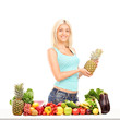 Young woman holding pineapple behind table full of fruits