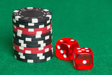 red and black poker chips and dice on a green casino felt
