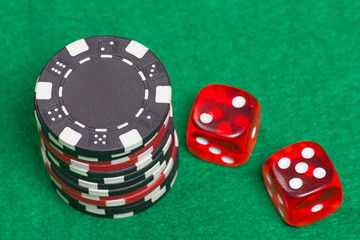 black and red poker chips and dice on a green felt