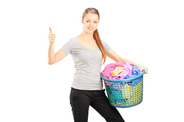 Young woman with laundry basket full of clothes giving thumb up