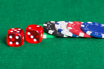 colorful poker chips and dice on a green felt