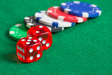 red dice on a casino table with chips